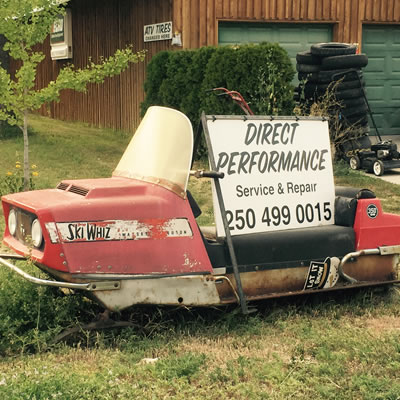 A picture of a vintage Ski-Whiz snowmobile with an advertising sign sitting on top of it.