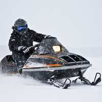 A rider on a vintage Arctic Cat Pantera snowmobile.