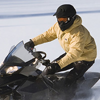 person riding a snowmobile and wearing a yellow jacket
