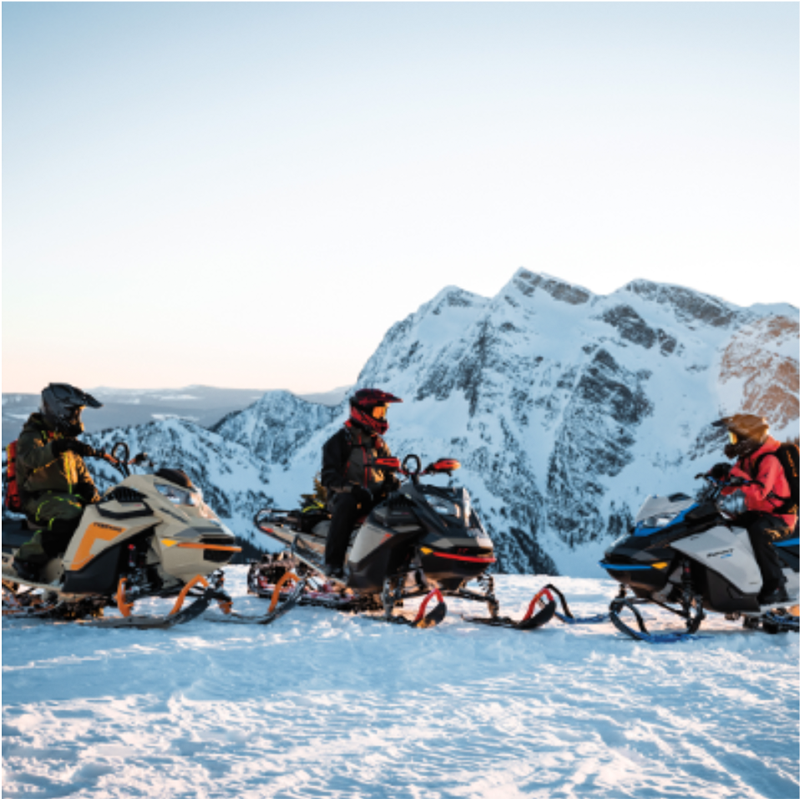 Three snowmobilers form a semi-circle on top of a snowy mountain.