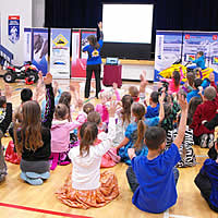 A group of children in a gym with their hands up.