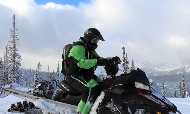 A man sitting on his snowmobile.