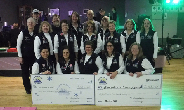 Volunteers with the Mission Ride of Prairie Women on Snowmobiles are lined up with two large imitation donation cheques in front of them.