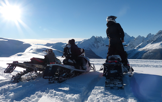 Two snowmobilers looking at mountains in the distance.