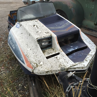 A rusty and dented Polaris TX 250 snowmobile.