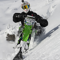 A man in a white helmet on a green snow bike.