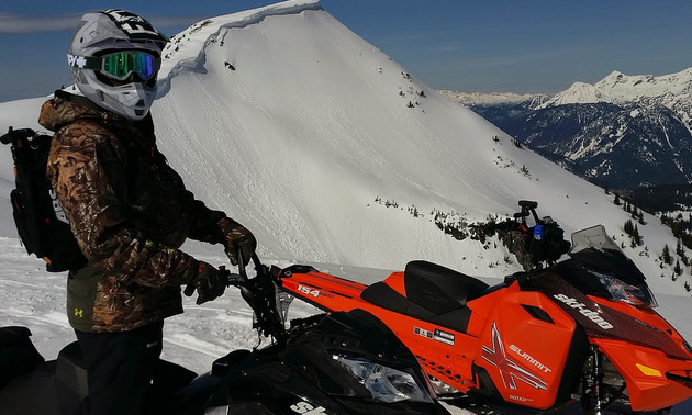 A sledder stops for a view and a rest in the mountains around Revelstoke.