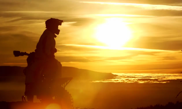 Ronnie Renner looking into sunset on a Timbersled snowbike