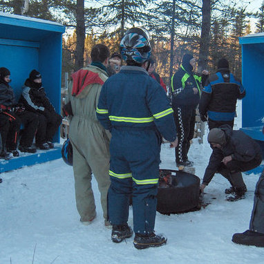 Snowmobilers are standing around and relaxing at one of three picnic areas on the Watt Mountain loop.