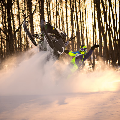 A snowmobiler waves as he's doing a tailstander in the snow.