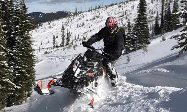 Snowmobiling sidehills.