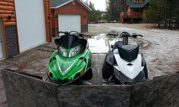 A skidoo and a Artic Cat sled on a trailer.