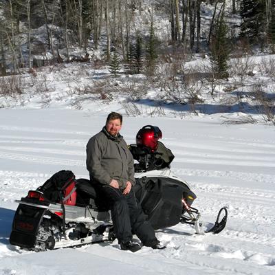 Scott Kjarsgaard sitting on his Ski-Doo Rev in the sunshine.