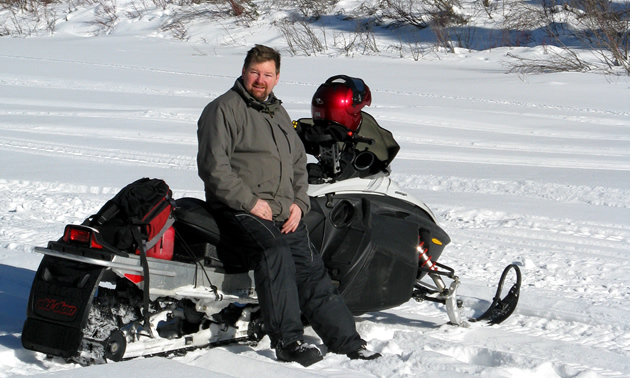 Scott Kjarsgaard sitting on his Ski-Doo Rev in the sunshine.