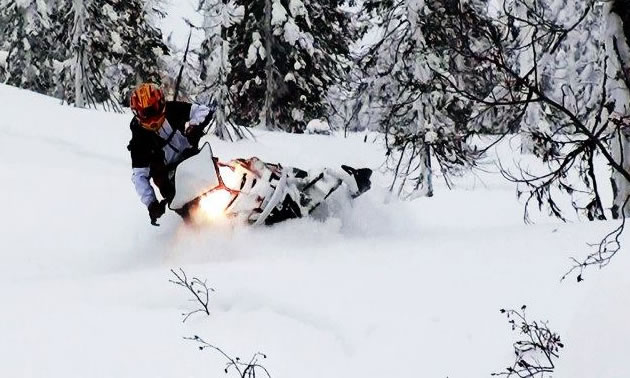 A woman in a red helmet riding a snowmobile through deep snow.