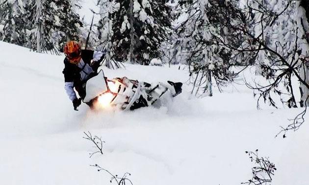 A woman in a red helmet riding a snowmobile through deep snow.
