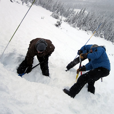 Three avalanche rescuers demonstrating the proper shovelling technique.