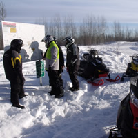 Snowmobilers looking at a map at the trailhead.