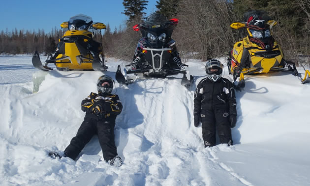 Two people in snowmobile suits laying against a snow bank.