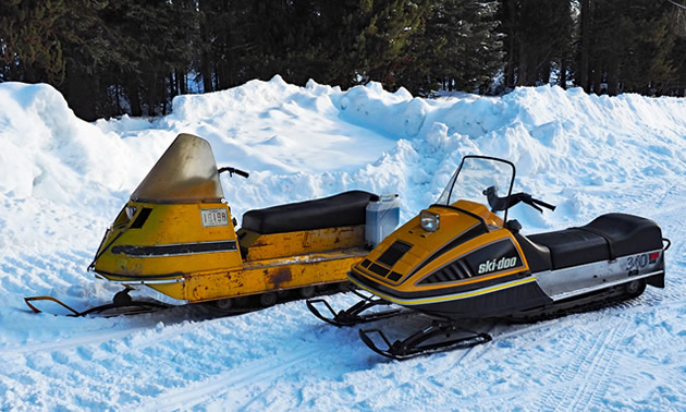 Two vintage Ski-Doo snowmobiles sit side by side on a snow covered trail