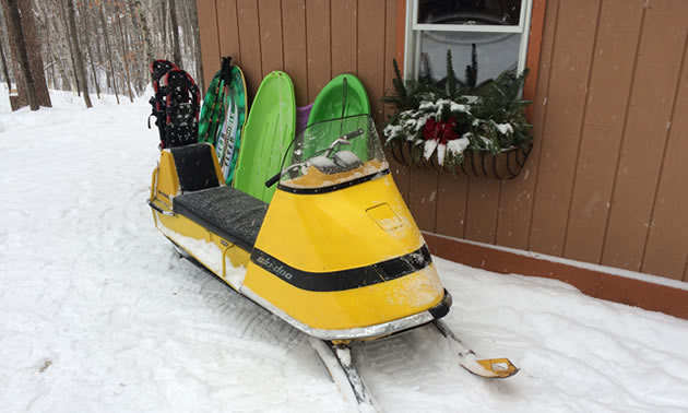 Ski-Doo sitting in front of cabin.