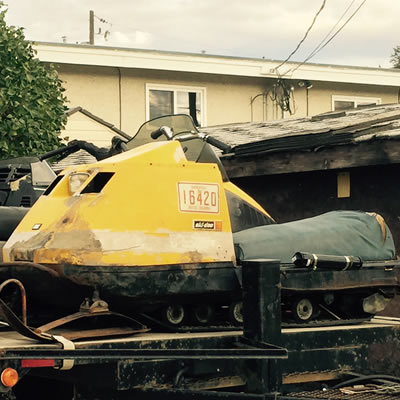 Picture of old yellow Ski-Doo Elan on flatbed truck.
