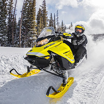 Picture of yellow and black Ski-Doo on snowy trail.