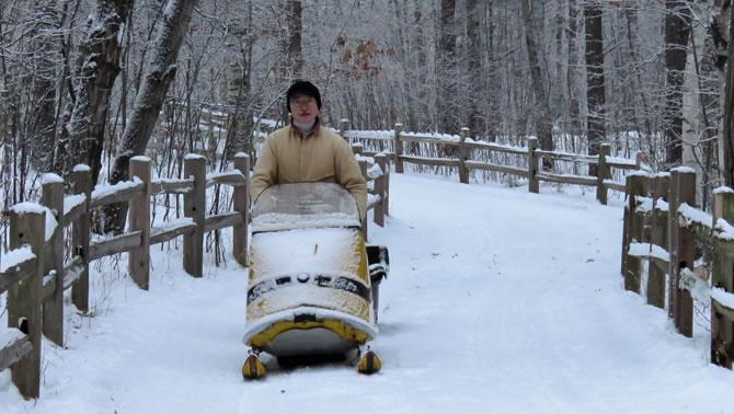 A man riding a Ski-Doo in winter