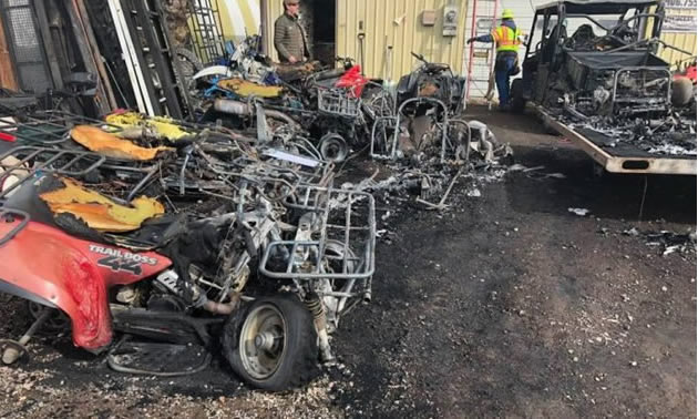 Burnt sleds and ATV's sitting outside a business.