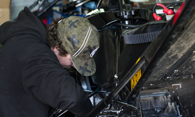 Mechanic working on a snowmobile.