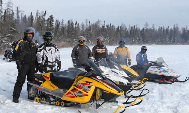 a group of people with parked snowmobiles