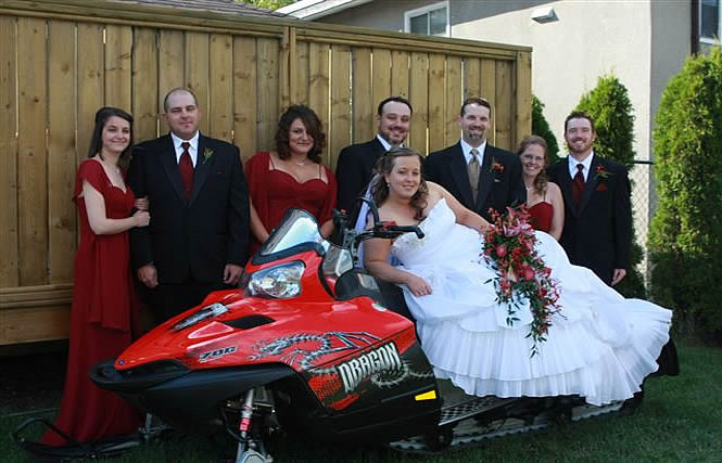 Bridal party gathered around a snowmobile