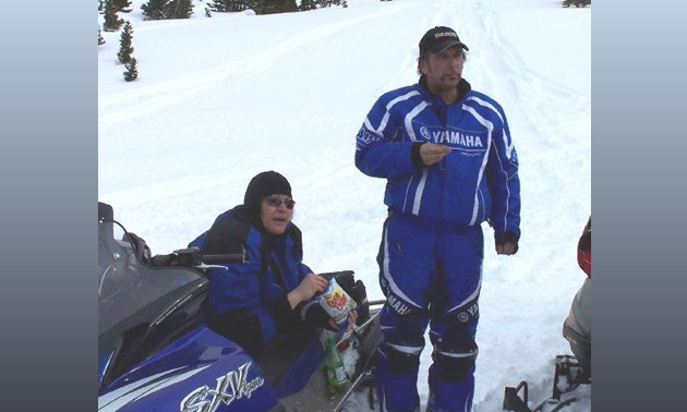 people on snowmobiles taking a break