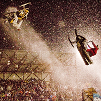 Two snowmobilers flipping through the air.