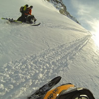 A photo of two guys riding tandem on a snowmobile.