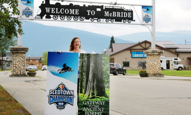 Loranne Martin, mayor of McBride, B.C., displays new signage downtown to promote the city's 2018 SledTown ShowDown victory.