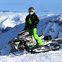 Curtis Hofsink is standing on his sled on a ridge that is overlooking blue sky and mountains.