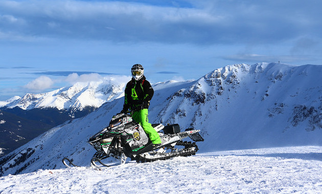 Curtis Hofsink sitting on his bright yellow sled with the mountains and blue sky in the background.