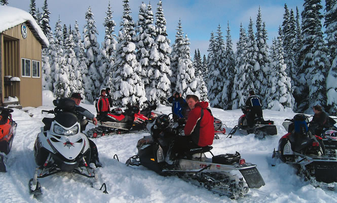people sitting on snowmobiles in front of a cabin with forest behind