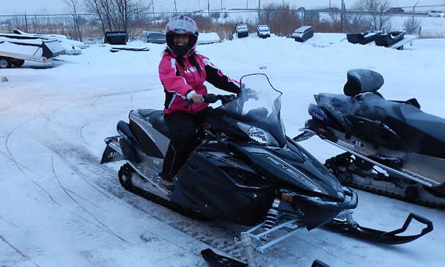 A woman on a stationary snowmobile