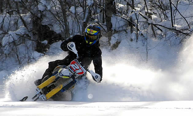 A rider rides his ski bike through the powder.