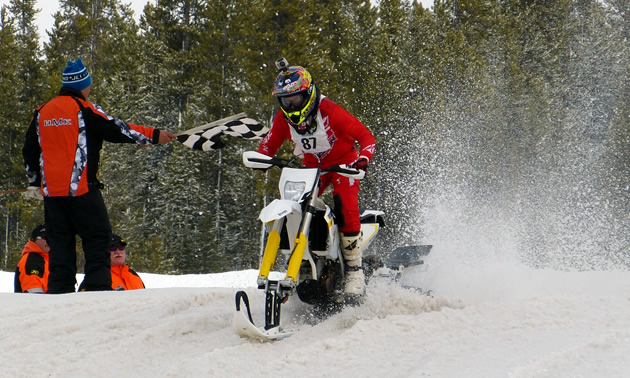 FMX rider Justin Homan taking the checkered flag in a snow bike race.