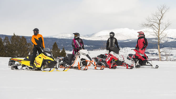 Group of snowmobilers on snowy mountainside
