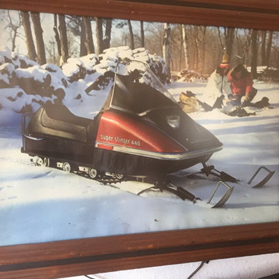 Back-lit barroom sign with a picture of a Scorpion snowmobile and couple sitting around a campfire.