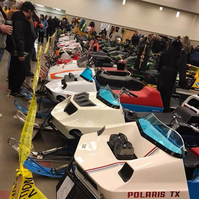 Line-up of snowmobiles in indoor arena.