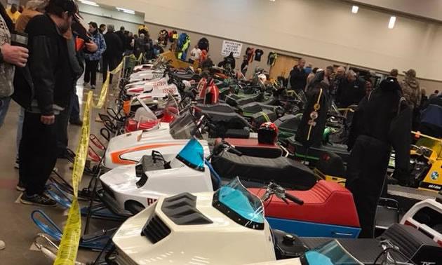 Line-up of snowmobiles in indoor arena.