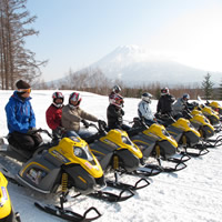 A group of snowmobilers in Japan sitting on sleds in a line.