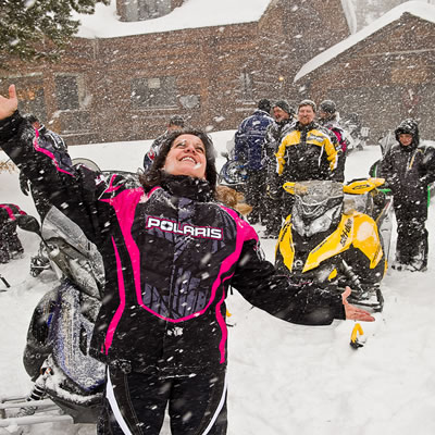Snowmobiler throwing her hands up in joy at the snow falling.