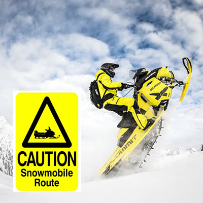 Person on snowmobile, with 'Caution - Snowmobile route' sign.