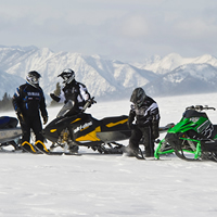 A group of snowmobilers sitting on top of a mountain.